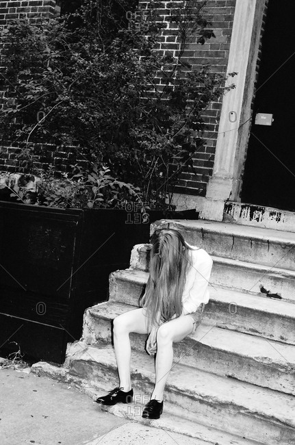Young woman looking forlorn on a stoop