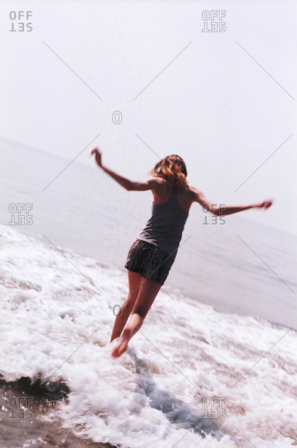 Carefree woman playing in ocean surf