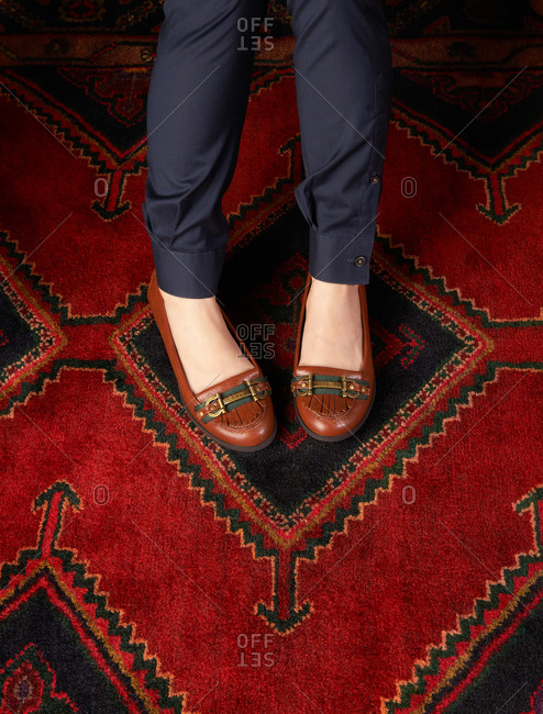 Woman's loafers on a deep red carpet