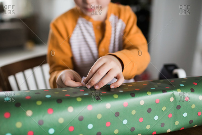 Child wrapping Christmas presents