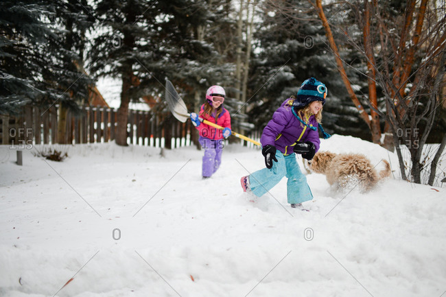 Girls and family dog playing in the snow