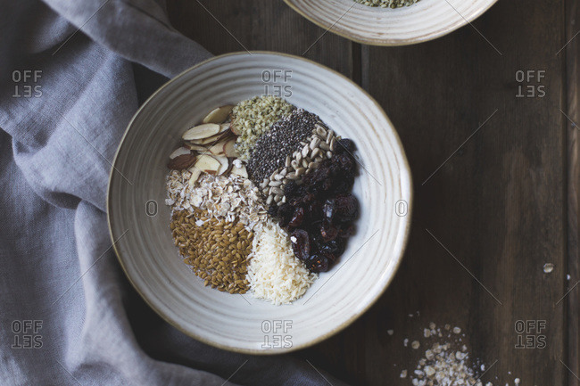 Overhead of dry oatmeal in dish with seeds and dry fruit