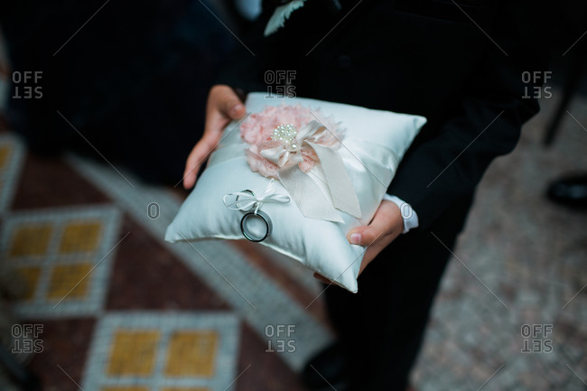 Boy holding pillow with wedding rings