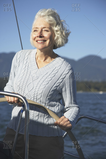 Senior woman standing at the helm of a sailboat