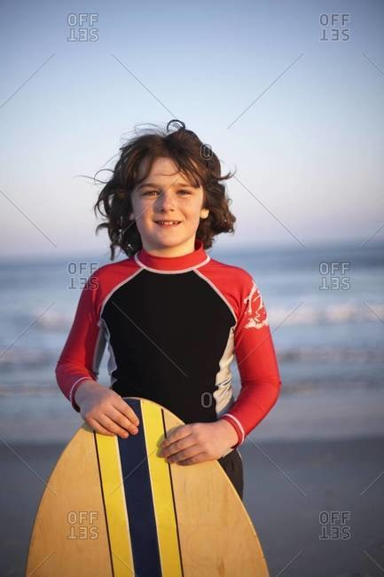 A boy standing behind his surfboard at the beach