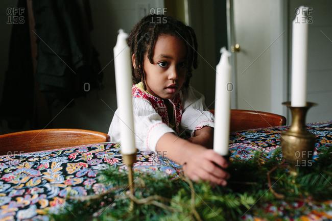 Girl placing Christmas candles on a table