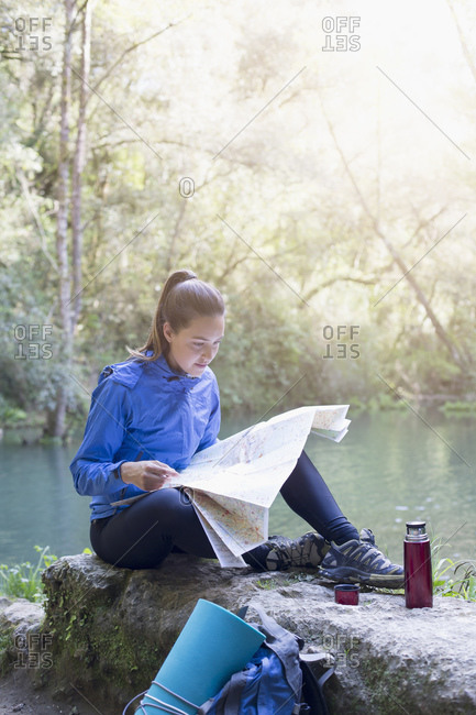 Woman reading a map by a river