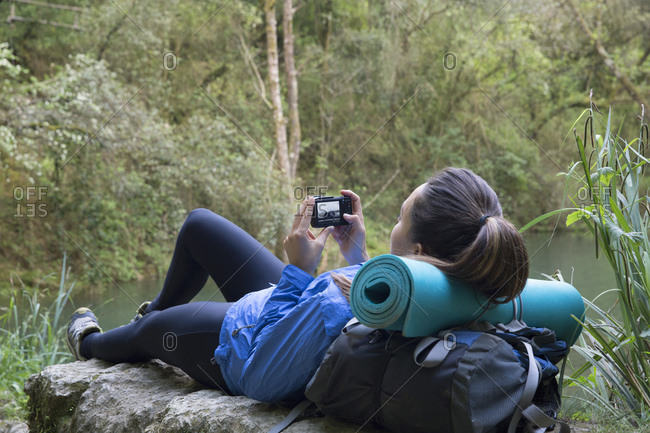 Woman lounging on rock by river looking at photos on camera