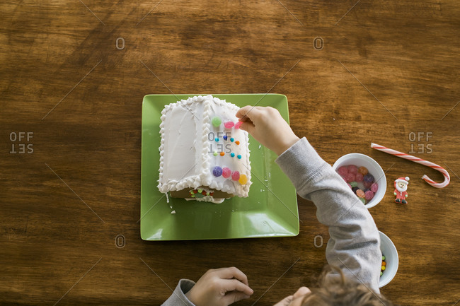 Boy decorating the roof of a gingerbread house
