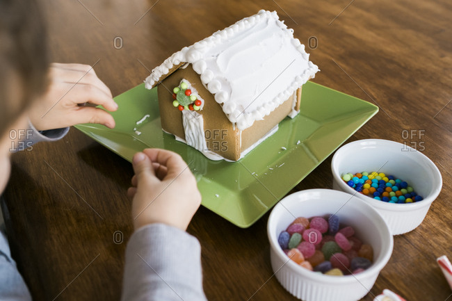 Boy putting candy on a gingerbread house