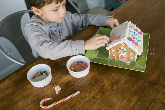 Boy putting gum drops on the roof of a gingerbread house