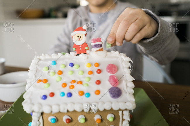 Boy placing candy on the roof of a gingerbread house with Santa
