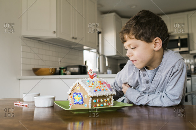 Boy looking at a decorated gingerbread house
