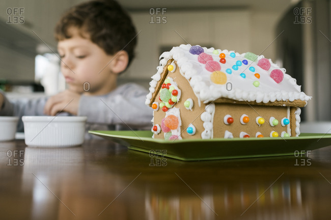 Boy sitting at a table with a decorated gingerbread house