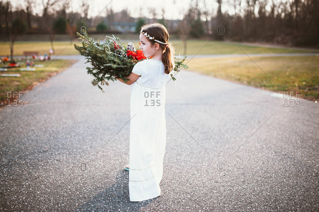 Back view of young girl holding Christmas grave blanket in cemetery