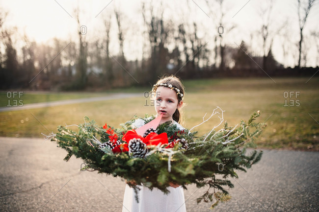 Young girl holding Christmas grave decoration in cemetery