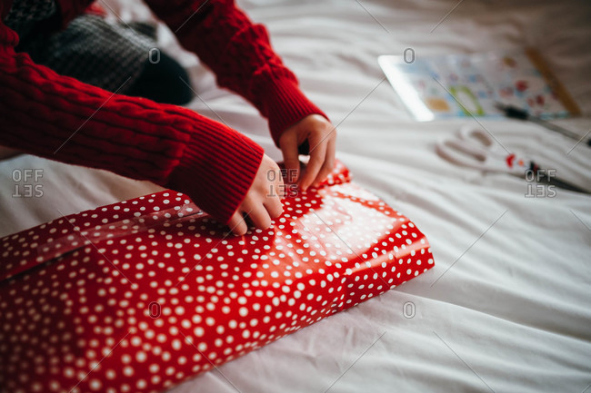 Child wrapping Christmas gift on bed