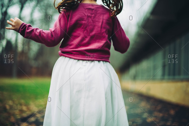 Back view of young girl in a fuchsia sweater and white skirt