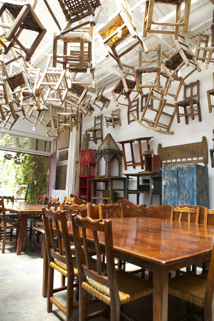 Buenos Aires, Argentina - November 9, 2010: Chairs hanging from ceiling above dining tables and chairs