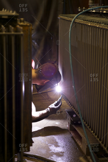 Welder working on a component of an electrical transformer in factory