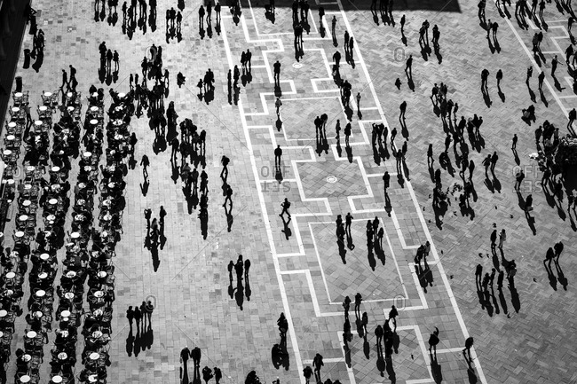 Silhouettes of people in a large plaza