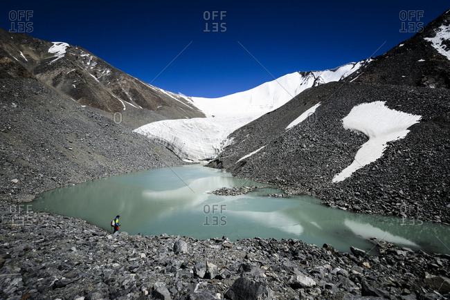 Man walking toward a pool of glacial water in the Himalayan mountains