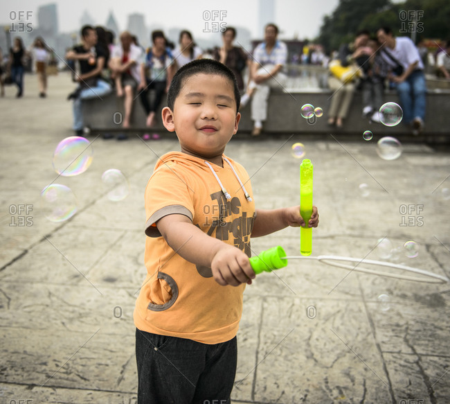 Little boy playing with bubbles in a park