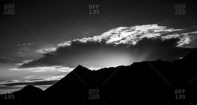 Sun rising over black mountain peaks