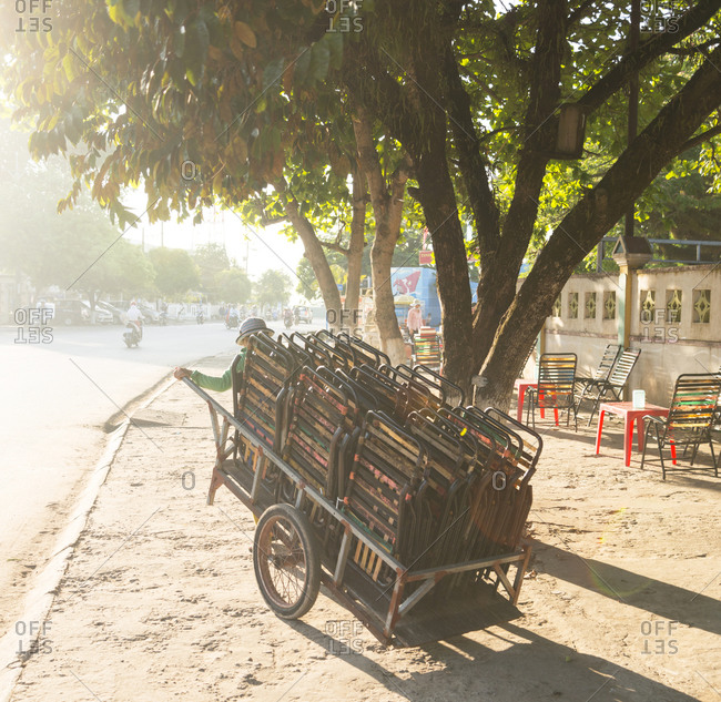 Woman pulls a trolley loaded with chairs in Duong Dong on Phu Quoc Island in Vietnam