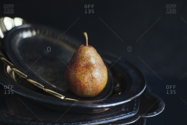 Pear sitting on a stack of metal platters