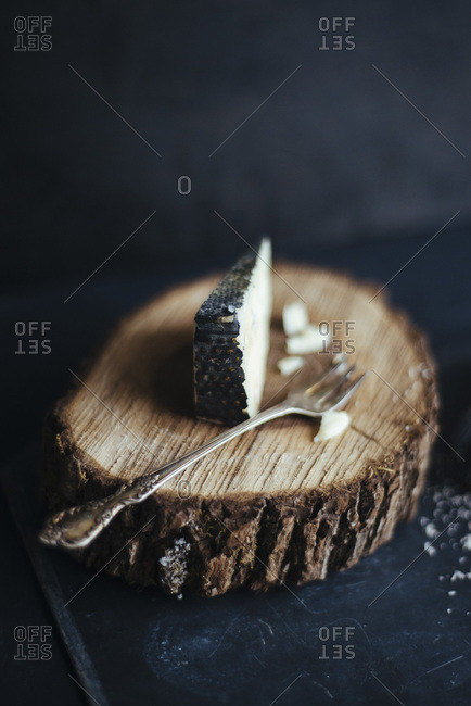 Wedge of cheese on piece of natural wood
