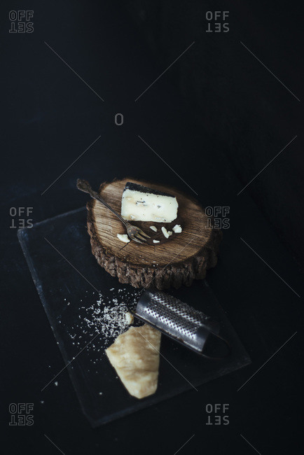 Cheeses with a piece of natural wood and grater