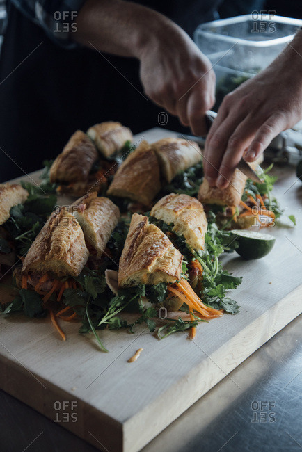 Chef dividing healthy sandwiches on baguette