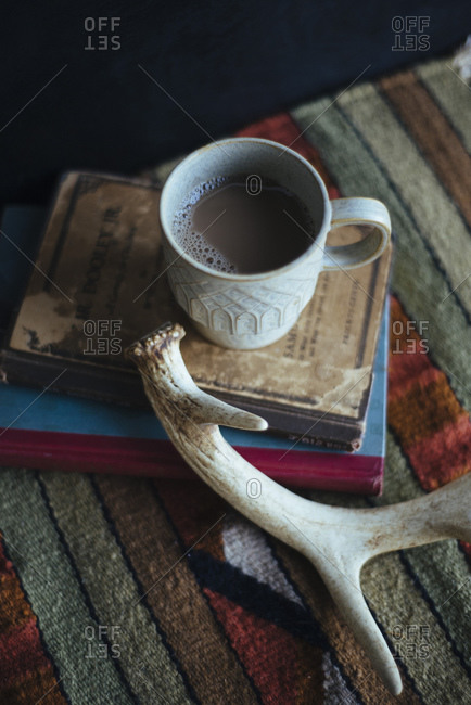 Cup of coffee on vintage books next to deer antler