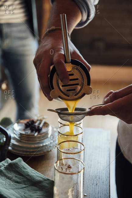 Pouring cocktails through a strainer from a shaker