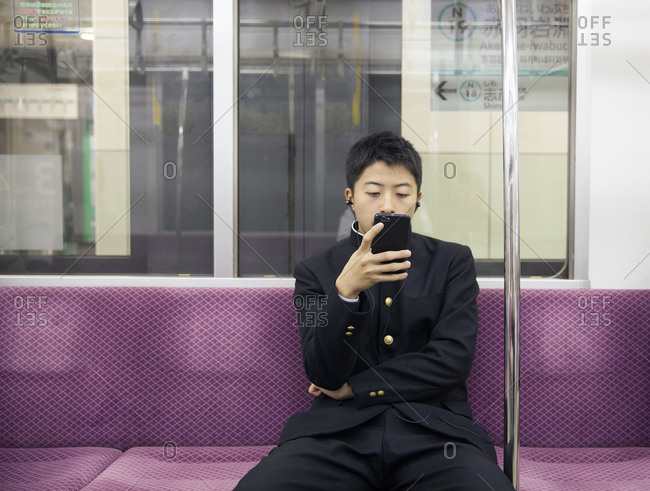 Tokyo, Japan - November 21, 2015: Young student riding subway with smartphone