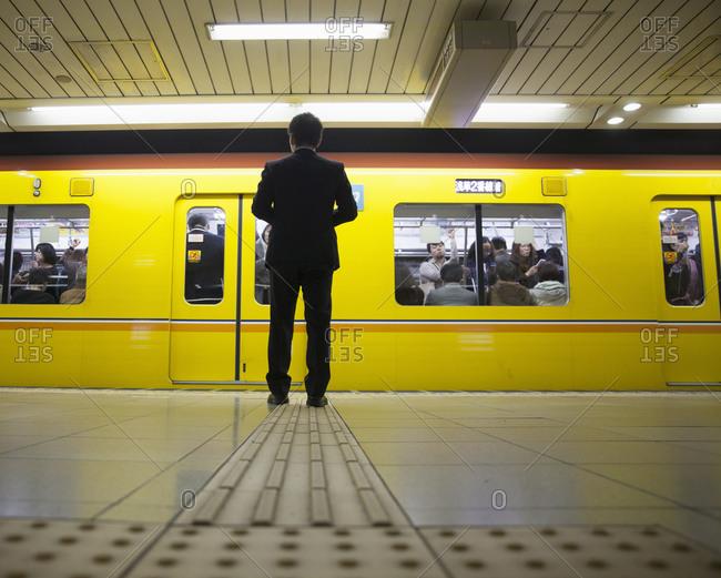 Tokyo, Japan - November 21, 2015: Businessman waiting for subway train