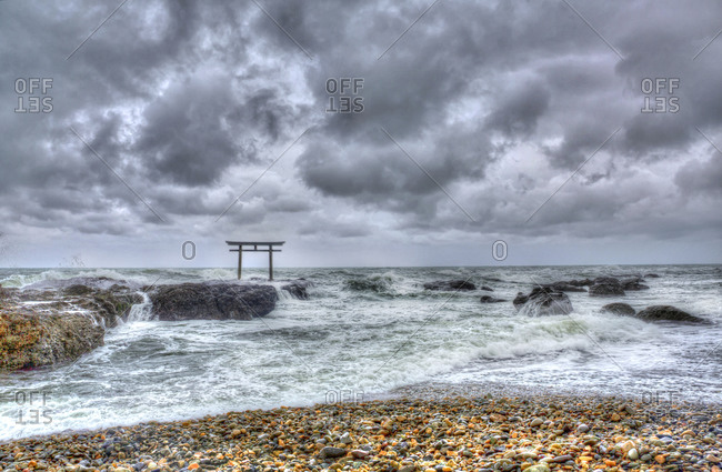 Torii gate on rocks in ocean under stormy skies, Japan