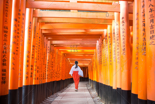 Fushimi Inari torii gate path with Shinto priestess, Kyoto, Japan
