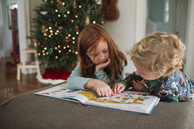 Brother and sister reading a Christmas themed book