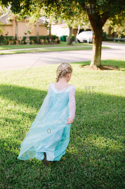 Young girl in princess dress walking on grass