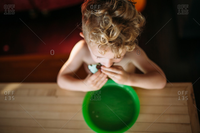Boy eating ice cream sandwich at table