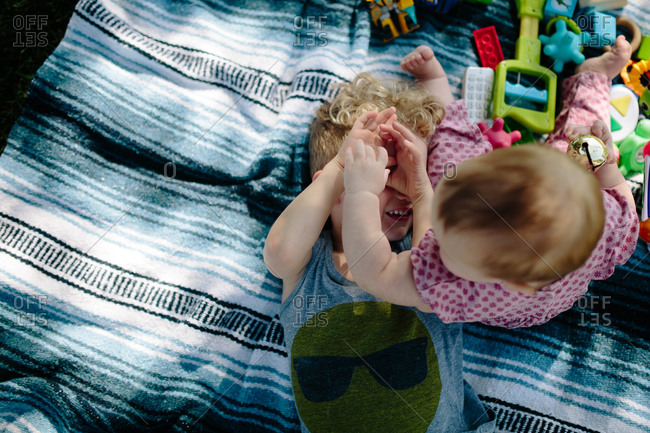Toddler and boy playing on blanket
