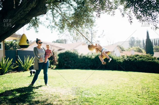 Mom pushing girl on tree swing
