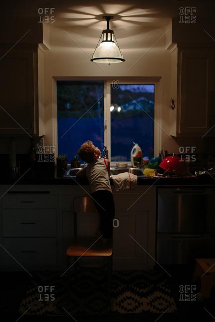 Boy looks up at kitchen light