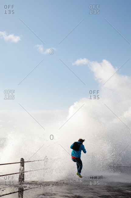 Man jumping on sea front with crashing waves, Sea Point, Cape Town, Western Cape, South Africa