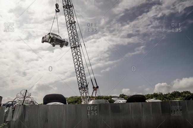 Crash damaged car hanging from crane at breakers yard