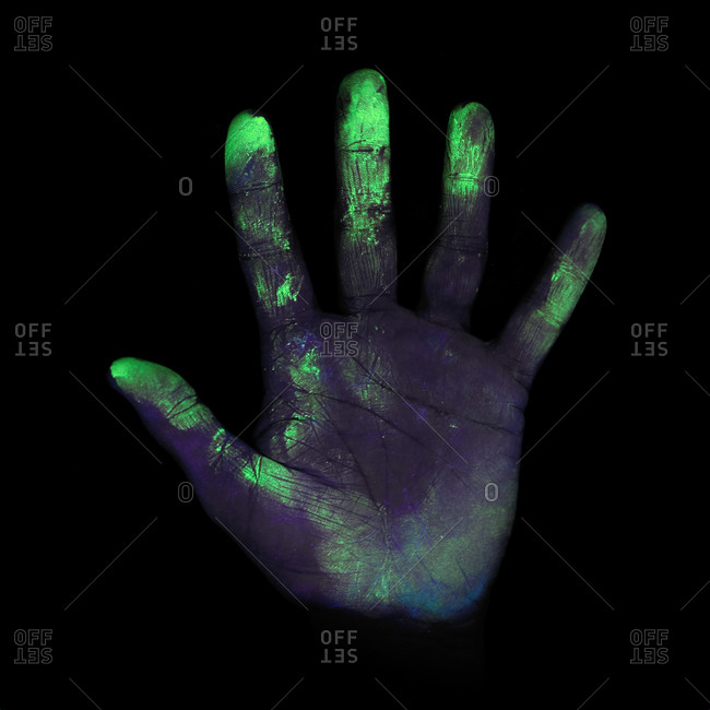 Ultraviolet (UV) light showing bacteria on a person's hand