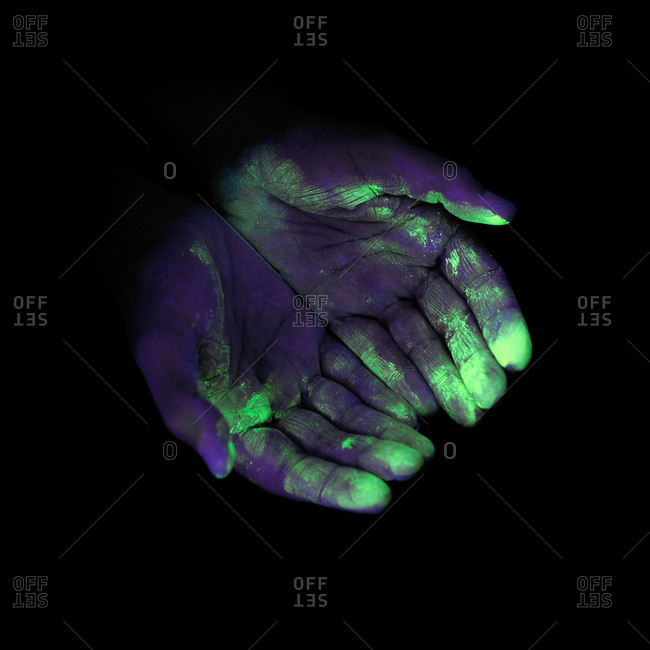 Ultraviolet (UV) light showing bacteria on a person's hands