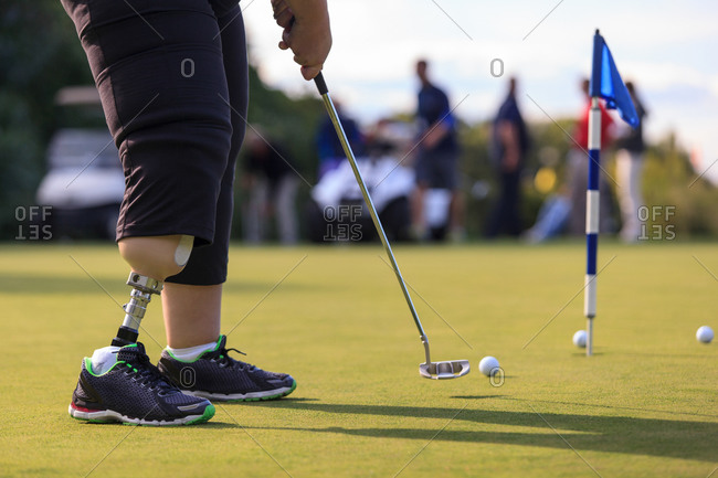 Woman with prosthetic leg at golf putting green